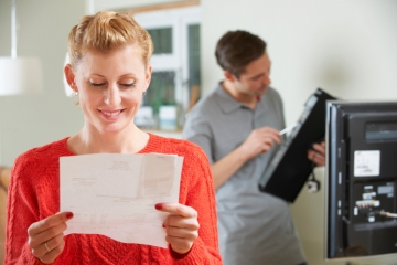 Happy Woman Looking At Bill For TV Installation